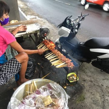 The satay is being grilled on the side of the road