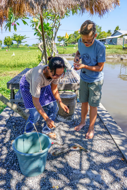 The Warung owner takes the fish off the hook