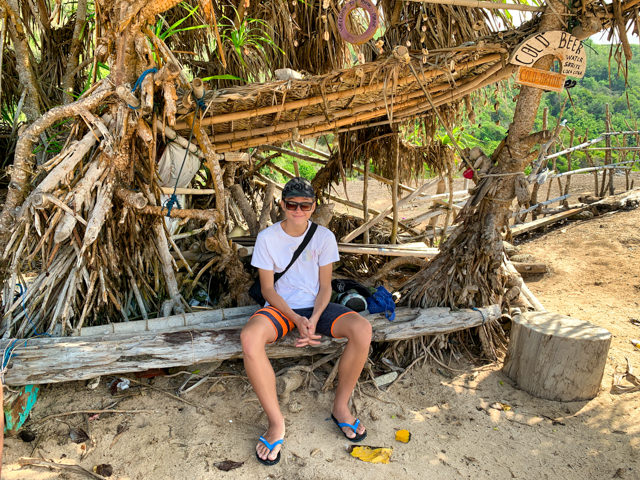 I'm relaxing in the shadow of a beach warung